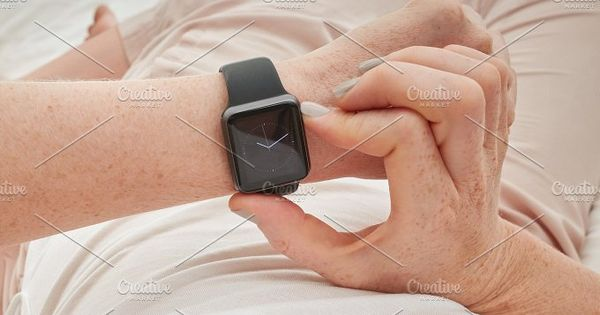 Closeup shot of woman checking time on her smart watch, she is lying on bed at home.