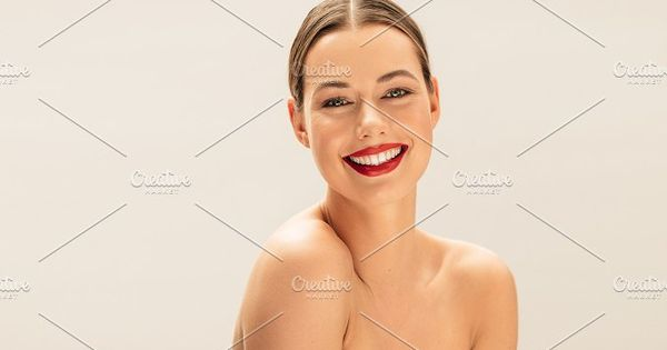 Portrait of happy young woman with beautiful skin. Pretty female model with beautiful smile against beige background.