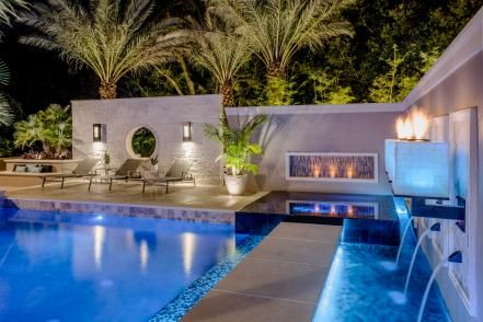 This Tropical Pool Features A Sunken Seating Area With Fire Pit And Is Surrounded By Attractive Stone Pave Tropical Pool Fire Pit Seating Area Fire Pit Seating