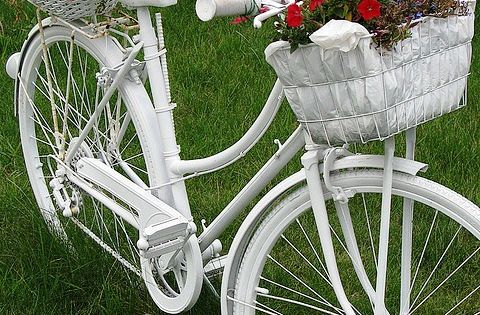 Pretty white bicycle with flower baskets. I need to find an old