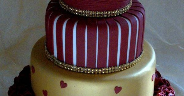 This is a four tier wedding cake with gold roses and burgundy