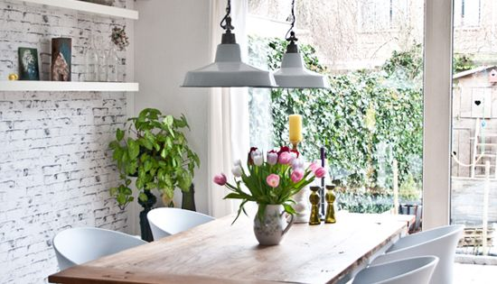 A relaxing dining room with industrial pendant lights over the dining table,