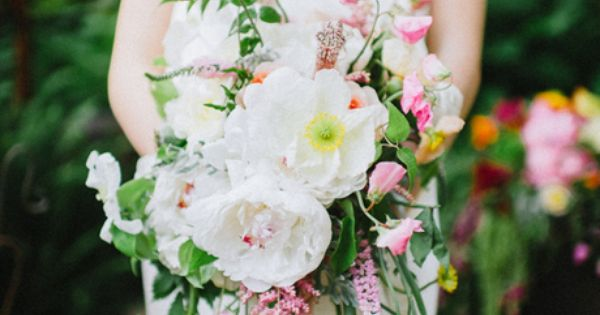 This voluminous, cascading bouquet features bright white peonies, poppies, and clematis. The addition of pink sweet peas, astilbe, and jasmine add pretty pops o