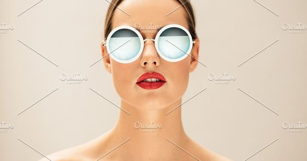 Close up portrait of pretty young woman with glasses against beige background. Female fashion model posing with sunglasses.