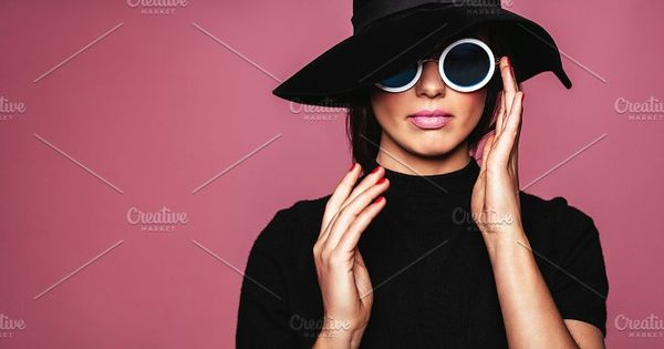 Close up portrait of stylish caucasian female model. Beautiful woman in hat and sunglasses posing over pink background.