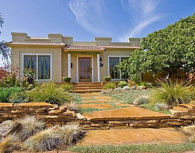 Drought-tolerant yard A low retaining wall of stacked flagstone has the effect
