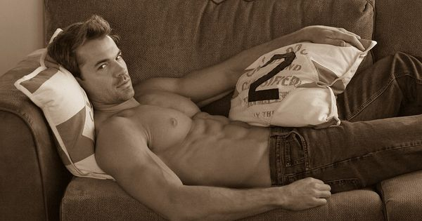 Model Chris Ryan laying on the couch wearing denim jeans