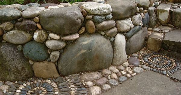 River rock retaining wall. pebble mosaic instead of flowers in the bed.
