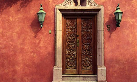 """Door on Slanted Street"" by Frans Alkemade. Bougainvillea over carved wood door,"