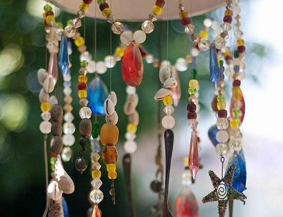 A garden wind chime made from a kitchen colander, some silverware, beads
