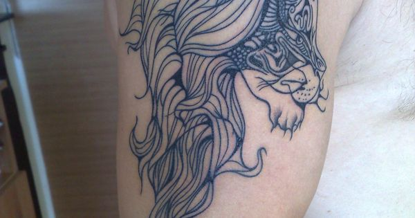Lion shoulder tattoo by Hurricane Tattoo. Tribal-esque. Nice line detail.