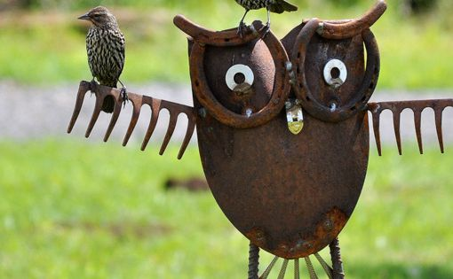 Garden art made from a shovel, rakes and horseshoes