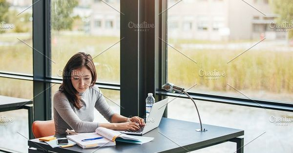 Young asian woman sitting in library searching information on laptop for her assignment. Young woman sitting at table reading book and using laptop.