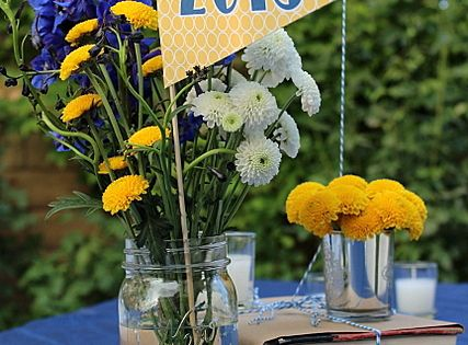 Awesome centerpiece. School color mums, mason jar, book, and pennant