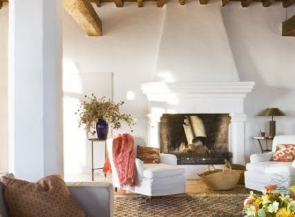 Spanish style living with rustic wood beams and fireplace