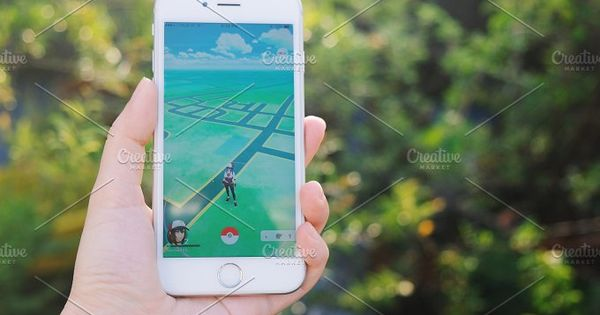 Hand holding Apple iPhone6s playing Pokemon Go game, Pokemon Go is a location-based augmented reality mobile game