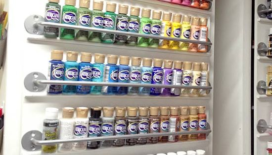 Organize craft paint on a cabinet door using towel bars ($2 @