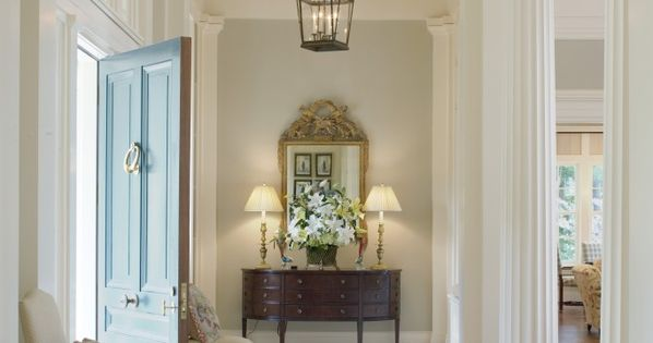 Gorgeous front door color and a n elegant foyer.