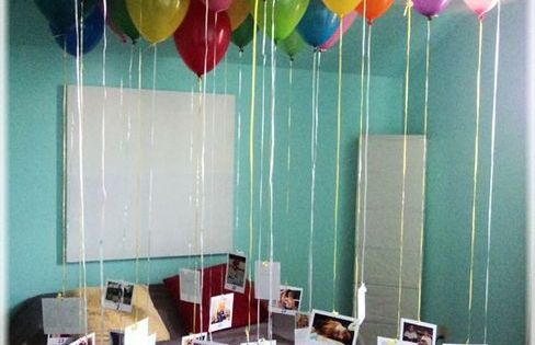 Balloons are attached to photos with a paragraph written on the back