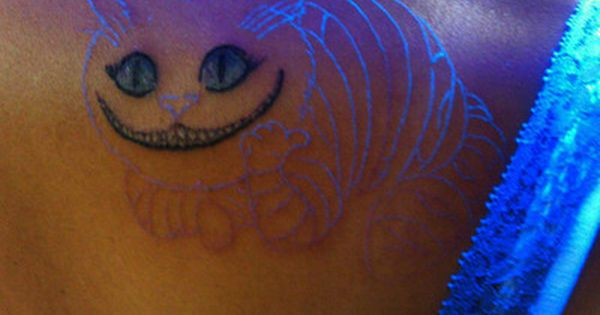 Cheshire Cat UV ink tattoo for body, and regular ink for mouth.