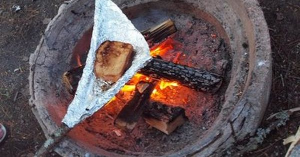 making grilled ham and cheese while camping using a stick and aluminum