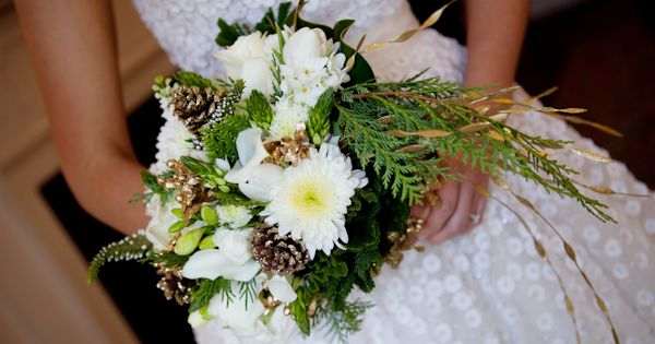 White mums, were mixed with gold pinecones, evergreens, star of bethlehem, white mini callas, tulips, and white freesia. This is a Winter bouquet. Photography by Genevieve Leiper.