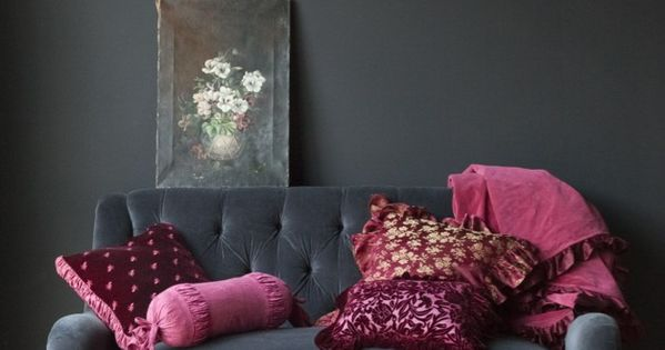 dark grey velvet sofa, dark grey walls with raspberry pillows