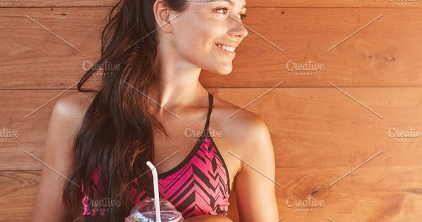 Vertical shot of fit female model with a glass of fruit juice after gym session standing against wooden background. Sportswoman holding glass of juice and looking away.
