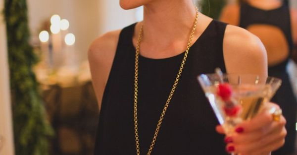 Love this whole holiday party look... black shift dress + long gold