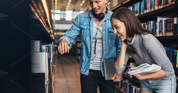 Image of happy young man and woman standing by book shelf in library and looking for books. Students at college library looking for books.