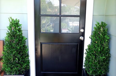 black front door glossy boxwood topiaries plants potted charcoal gray ceramic planters