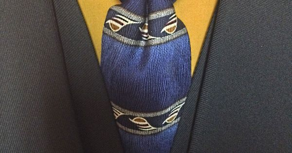 Many shades of blue with striping accents are present in this necktie arrangement.