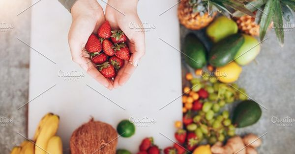 Top view shot of a female hands holding fresh strawberries over chopping board with fruits. Woman holding a handful of fresh strawberries.