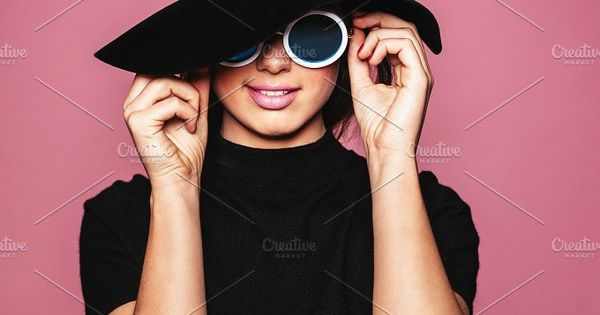 Close up portrait of beautiful young woman standing against pink background. Female model wearing hat and stylish sunglasses