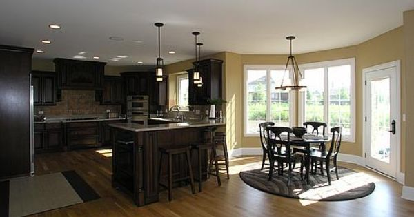 dark cabinets with light granite  stainless steel appliances  light wood floors  peninsula  and