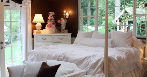 Dark walls, white ceiling, light wood floors, white bed, slipcover sofa