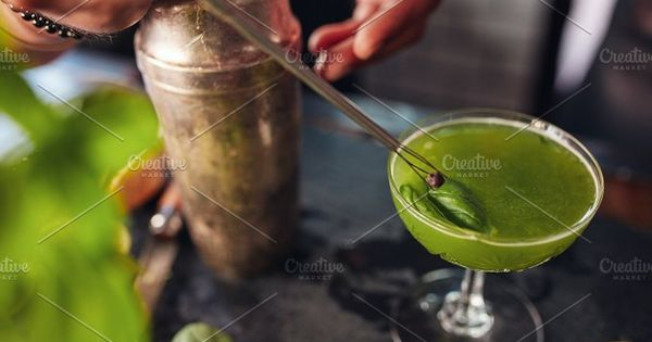 Close up shot of barman hands garnishing fresh green cocktail with a black peppercorn seed. Bartender preparing basil smash cocktail.