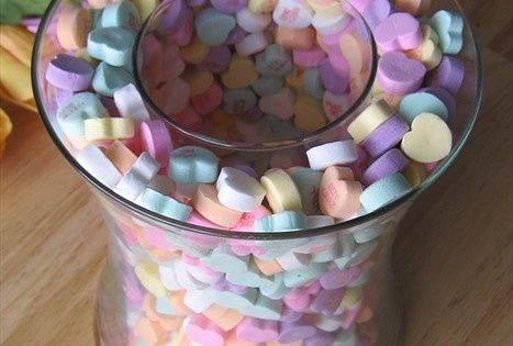 Take two different size vases and sprinkle candy hearts between them and