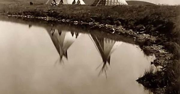 Two tepees reflected in water of pond, with four Piegan Indians seated
