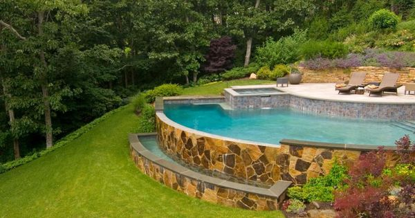An Arc Shaped Pool With A Spa Is Built Into The Hillside