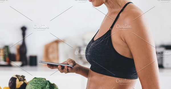 Side view of beautiful young woman standing in kitchen with bowl of fresh berries and reading text message on her mobile phone. Fit young woman in kitchen in morning.