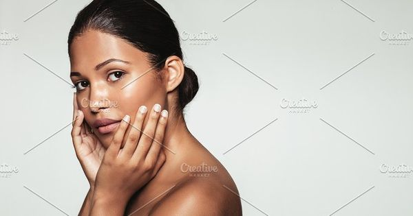 Portrait of beautiful female model with hands on her face looking at camera. Young woman with clean and healthy skin posing against grey background.