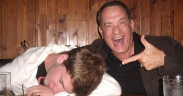 Tom Hanks grabs a random drunk guy's phone for a photo op.