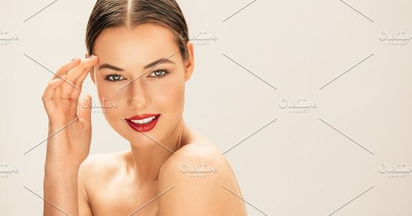 Close up portrait of beautiful woman with perfect skin and face looking at camera. Female fashion model wearing red lipstick with copy space.