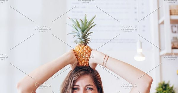 Portrait of happy young woman holding a pineapple on her head. Beautiful caucasian female at juice bar.