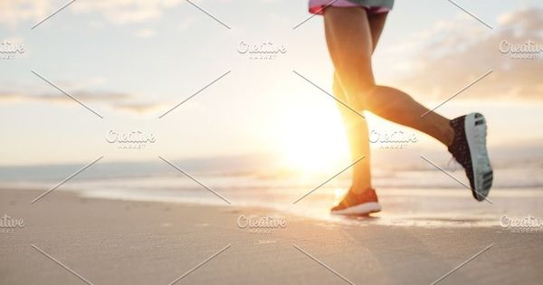 Feet of young woman jogging on the beach. Fitness female on morning run at sea shore.