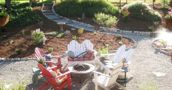 A gravel patio features Adirondack chairs and a fire pit ...
