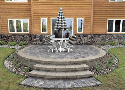 a raised paver patio blends colors and textures to complement the natural stone around the house - Raised Patio Ideas