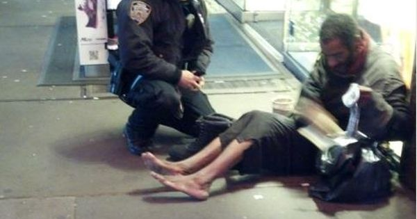 New York City Police Officer Larry DePrimo presenting a barefoot homeless man