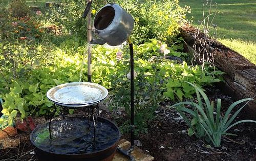 Outdoor fountain. A tea kettle continuously pouring water into a birdbath while